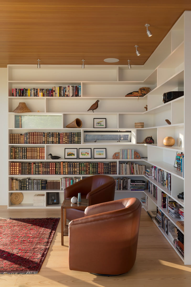 This reading nook is formed by walls of bookcases, which flow seamlessly out ofthe smaller scattered window pattern. #Bookshelves #Shelving