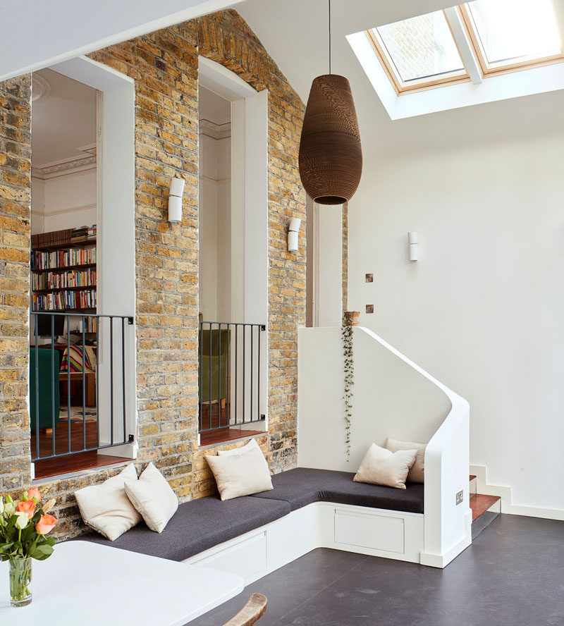 Inside this modern extension, there's elements of the original home on display, like the large brick wall, that provides a separation from the old and new areas of the home. A built-in bench provides a small sitting area in the extension. #BrickWall #Bench #SittingArea #InteriorDesign