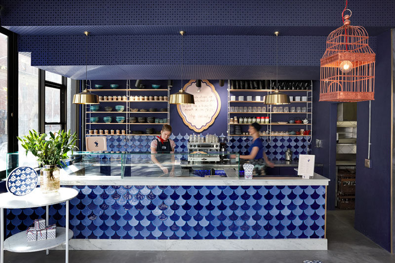 This cafe service area features blue feather-shaped ceramic tiles to create a handcrafted and detailed finish. #BlueTiles #InteriorDesign #CafeDesign #RetailDesign