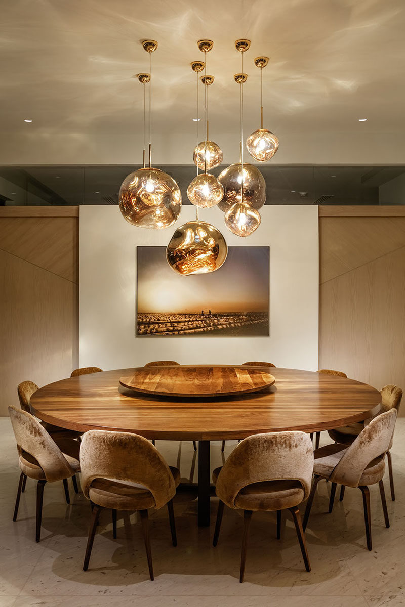 In this dining room, a collection of pendant lights hang above the large and round wood dining table. #DiningRoom #RoundDiningTable