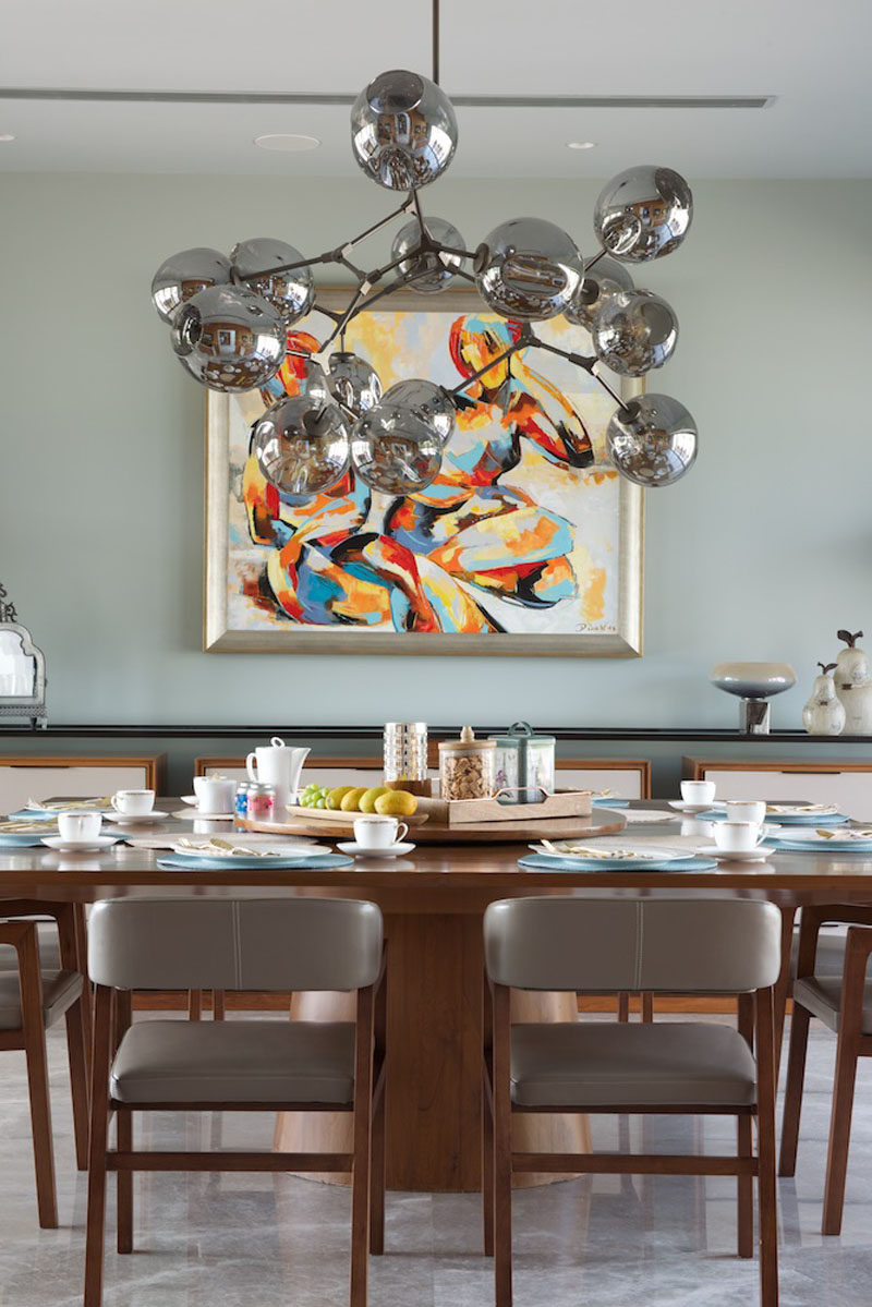 In this contemporary dining room, a large metallic chandelier hangs above a wooden dining table, while artwork brings in a touch of color to the room. #DiningRoom #InteriorDesign
