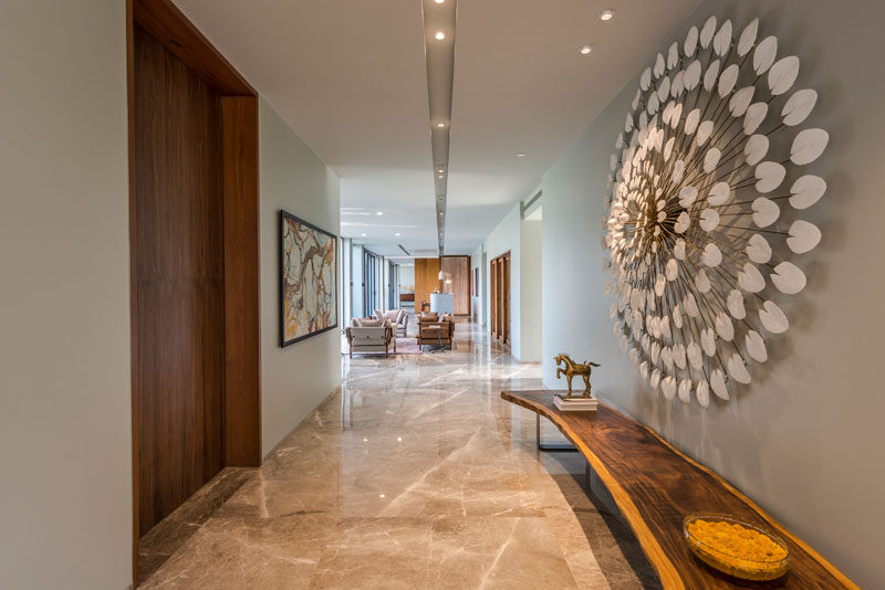 This contemporary house has an entry hallway furnished with a live-edge bench and sculptural artwork. #Entryway #Hallway #InteriorDesign