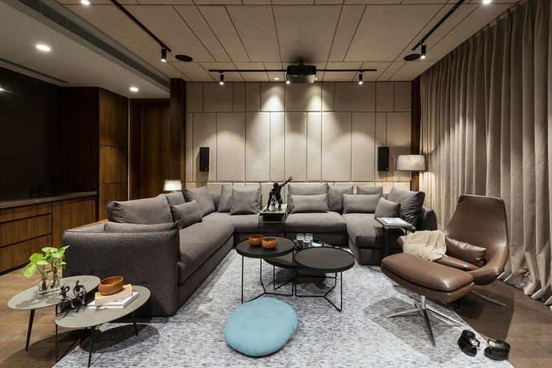 This media room uses dark tones in the furniture, fabric clad walls and ceiling, and track lights, to create the desired theatrical experience. #MovieRoom #HomeTheater #InteriorDesign