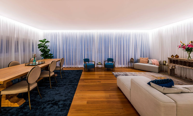 Full height backlit curtains, which run the length of the three walls of this modern studio space, provide privacy day or night and soften the space. Strip lighting running the perimeter provides soft diffused light in the room. #Curtains #BacklitCurtains #Lighting #InteriorDesign