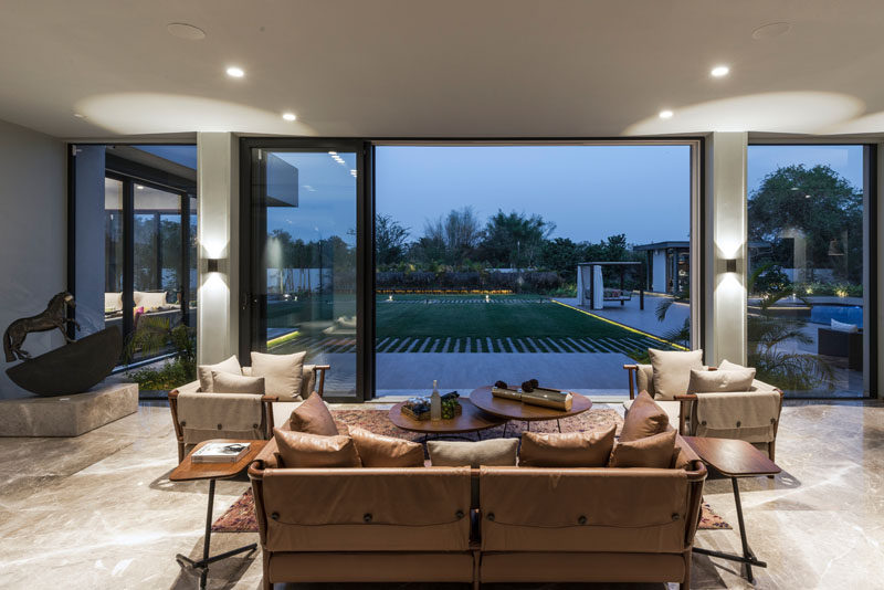 This contemporary living room has sliding glass walls that open up the interior to the backyard. #LivingRoom #SlidingWall #InteriorDesign
