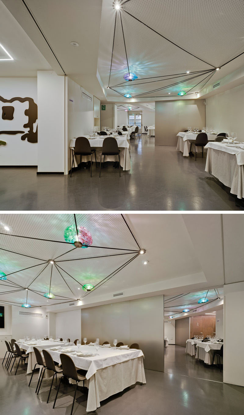 The upper dining area of this restaurant, which has various areas with large sliding walls and geometric lighting, can be used for entertaining groups of people. #Lighting #RestaurantDesign