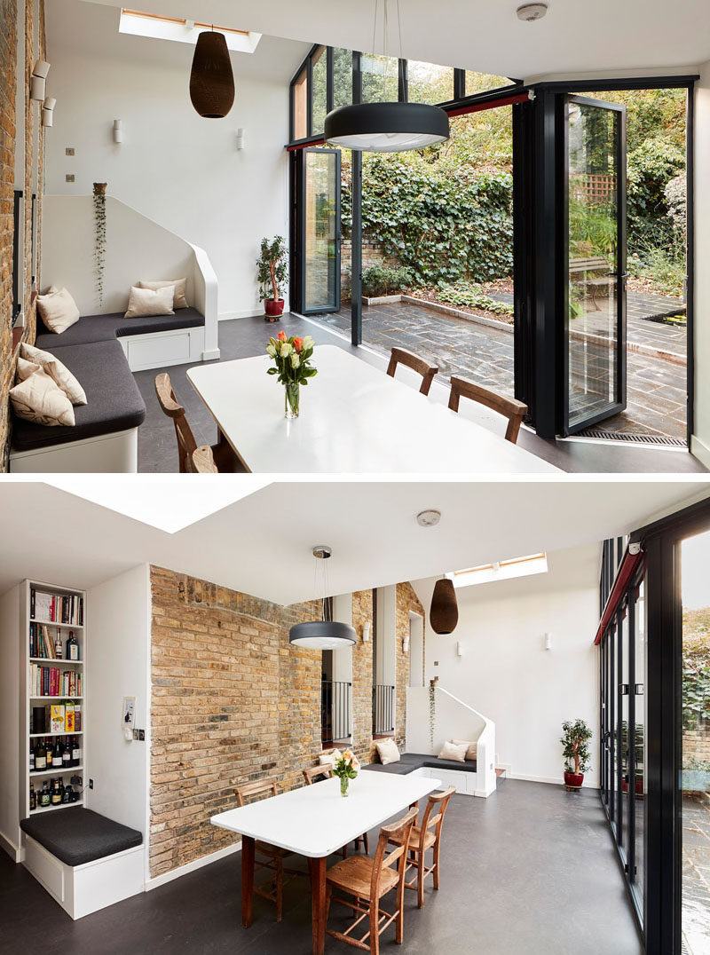 This modern house extension that has a sitting area, a dining area and a kitchen, opens up to the backyard with the use of folding glass doors. #ModernHouseExtension #ModernExtension #GlassWalls