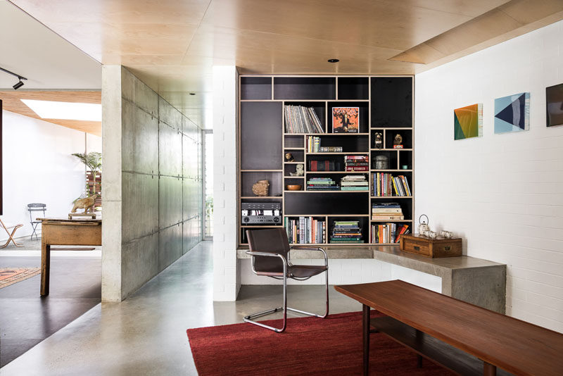 This modern house has a built-in black and wood bookshelf, and a concrete ledge. #Bookshelf #Shelving