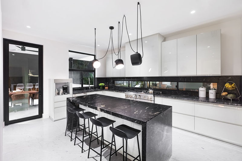 This modern kitchen is characterized by its black and white tones. #ModernKitchen #BlackAndWhite #KitchenDesign