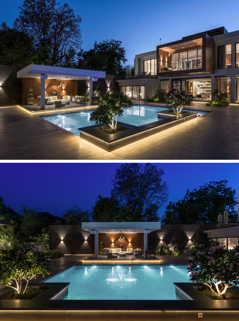 This modern house has a swimming pool with accent planters and a cabana. Hidden lighting has been used to create a luxurious atmosphere. #SwimmingPool #LandscapeDesign #Cabana