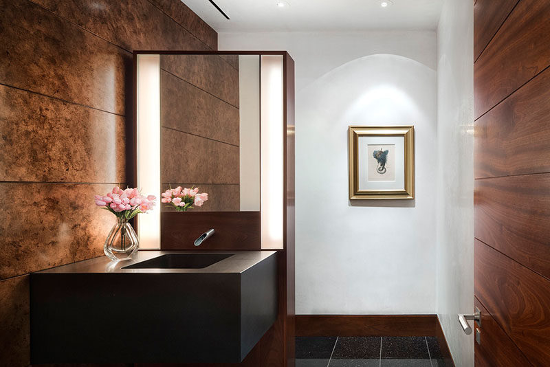 In this powder room, lighting has been used to highlight the artwork on the wall, and on either side of the mirror, soft lighting creates an ambient glow. #PowderRoom #Lighting