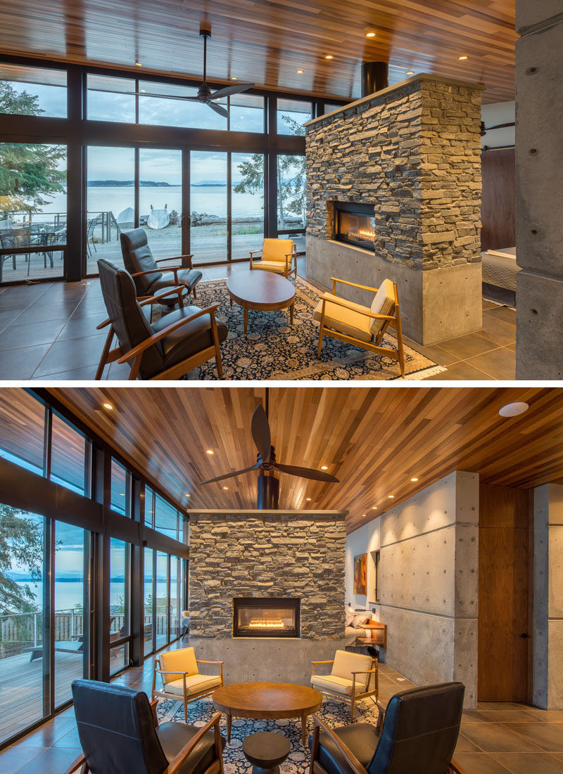 This modern waterfront cottage has a wood ceiling and stone work to bring a touch of nature inside. #Fireplace #StoneFireplace #BeachfrontCottage #WoodCeiling