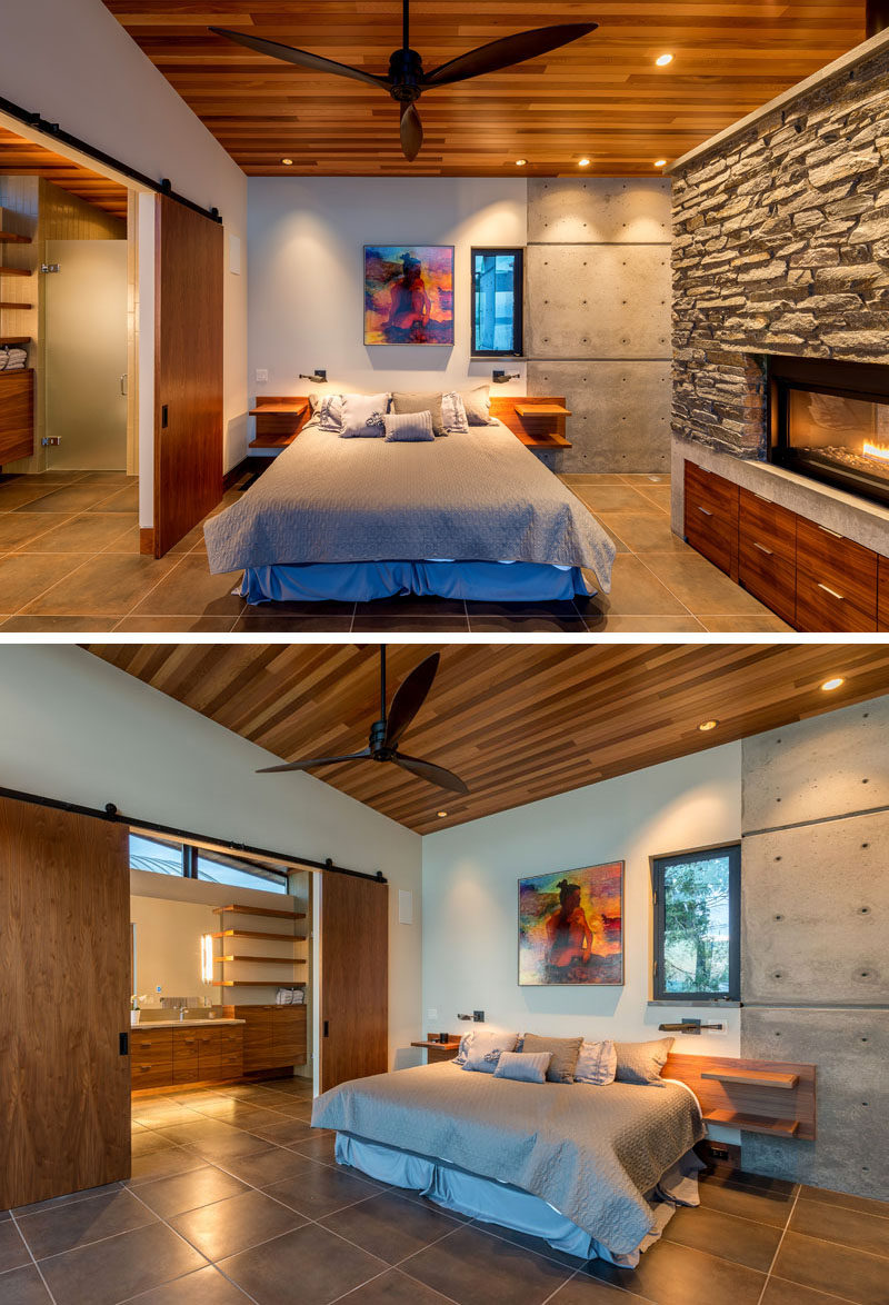 A set of sliding barn doors separate the bathroom from the bedroom, that features a stone, concrete and wood fireplace. #Bedroom #Fireplace #Doors