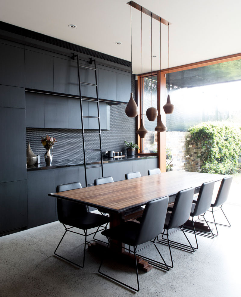 In this modern dining area, a ladder has been added to the black cabinetry to provide easy access to the upper cabinets. A collection of simple and elegant turned wood pendant lights help to anchor the dining table in the open plan interior. #DiningRoom #BlackInterior #BlackAndWood #DiningTable