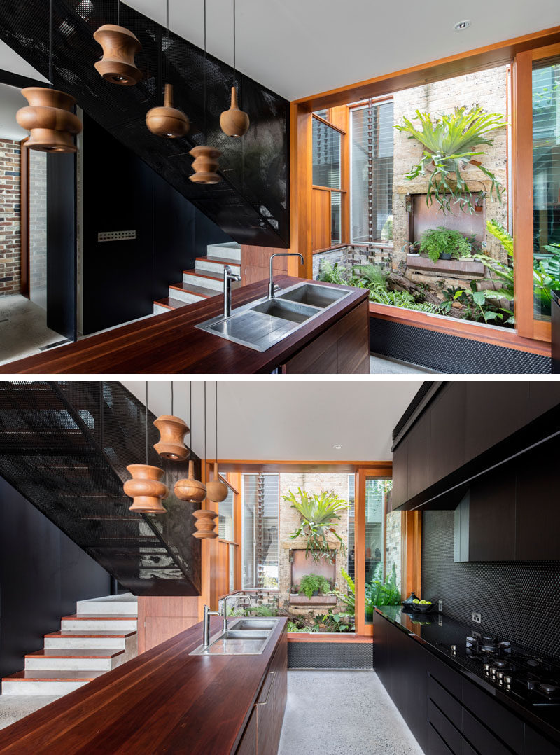This modern black and wood kitchen has a view of a small courtyard. #BlackKitchen #BlackAndWood #InteriorDesign #ModernKitchen