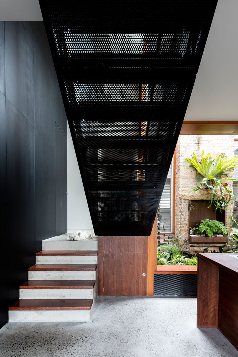 Wood, concrete and perforated metal stairs lead to the upper floor of this modern house. #Stairs #ModernStairs #StairDesign