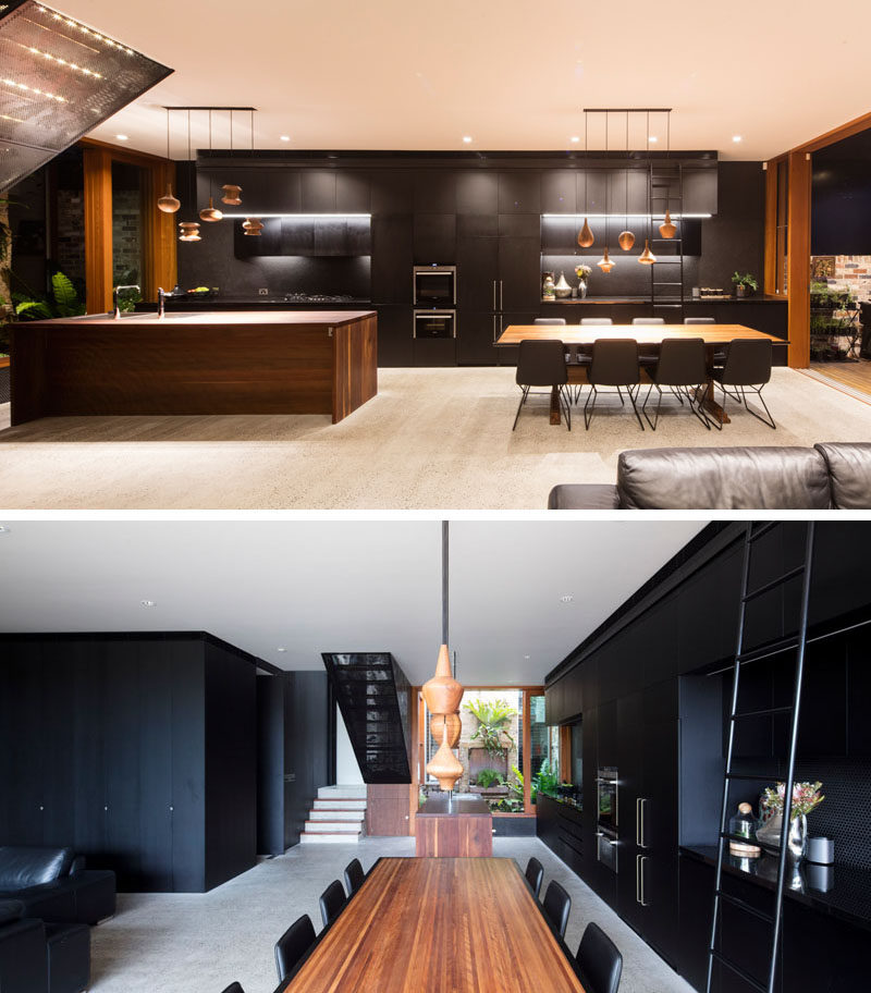 In this modern interior, black cabinetry runs the length of the wall, from the kitchen through to the dining area. #BlackCabinetry #InteriorDesign #BlackInterior #BlackAndWood