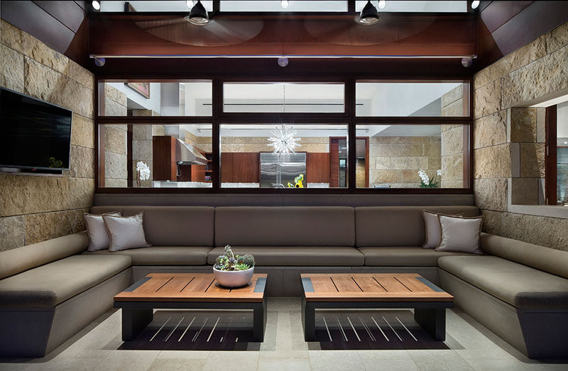 This modern house has an outdoor lounge filled with seating, and windows that provide a view of the kitchen inside. #OutdoorLounge
