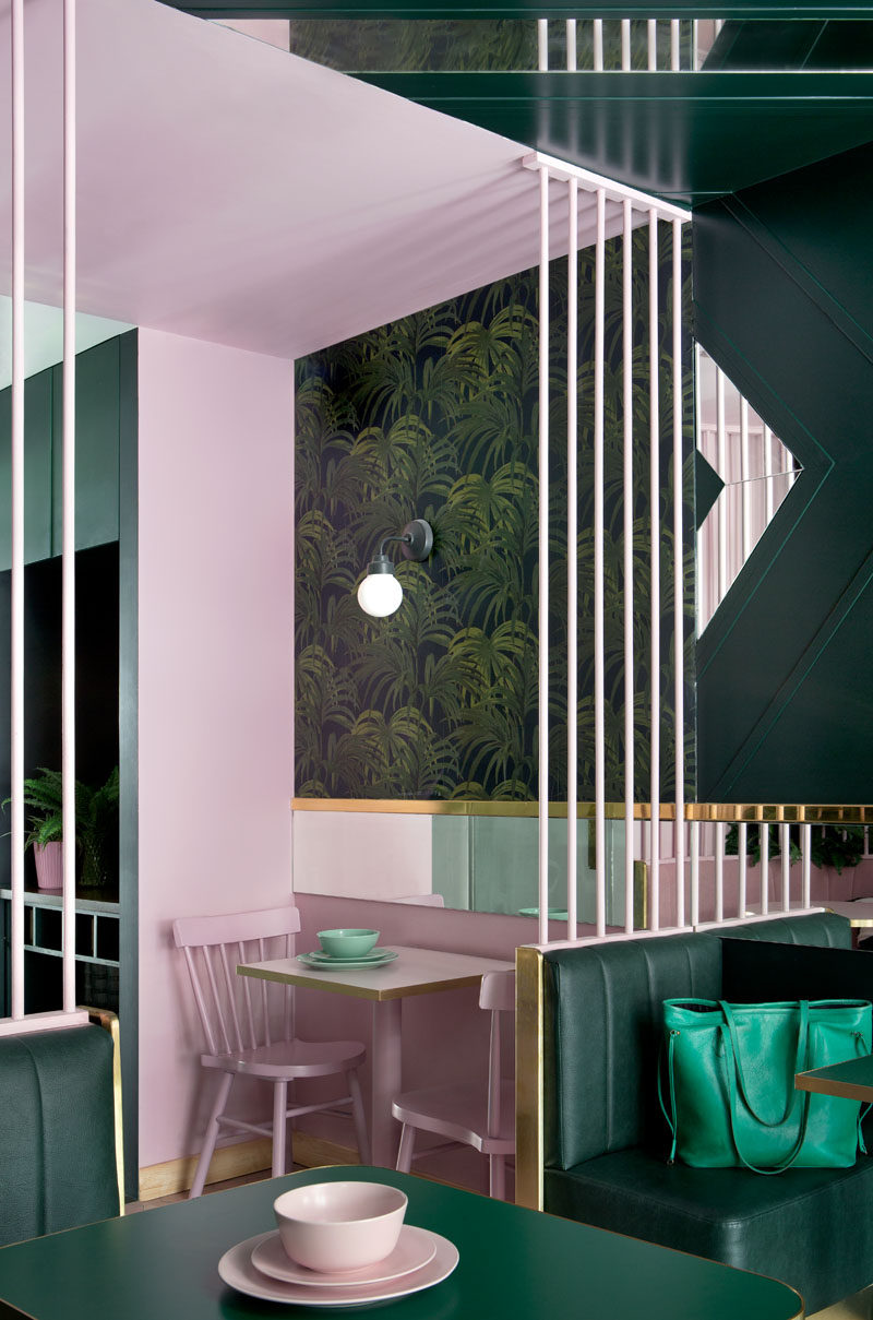 This green and pink modern cafe has a mixture of seating, with banquettes and smaller tables that can be enjoyed by individual diners and groups alike. #CafeDesign #InteriorDesign #ModernCafe
