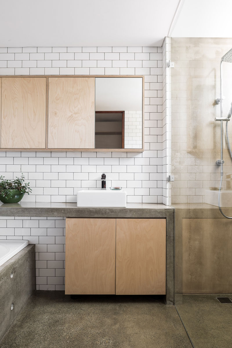 This modern bathroom features concrete counters and a concrete bathtub surround. White subway tiles and light wood cabinetry help to keep the bathroom bright. #BathroomDesign #ModernBathroom #Concrete