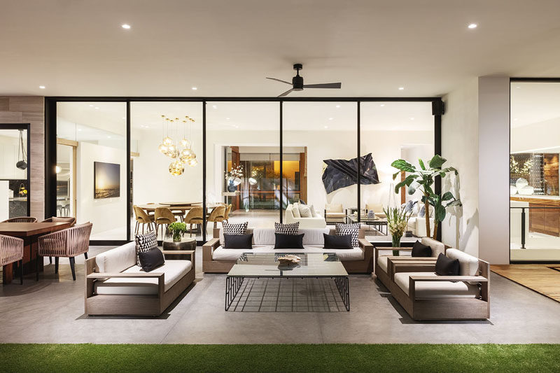 A wall of sliding windows can be opened to join the outdoor covered terrace with the interior spaces, making it a large open space for entertaining. #OutdoorLivingRoom #OutdoorSpace #GlassWall