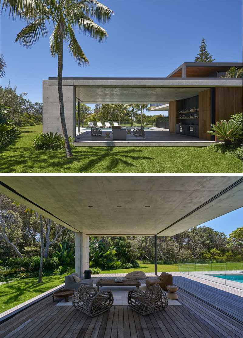 This modern house has a covered outdoor lounge area with a bar provides a place to enjoy the indoor / outdoor lifestyle by the pool, and if the weather turns, it can be closed off and protected from the elements. #ModernHouse #OutdoorSpace #OutdoorLounge