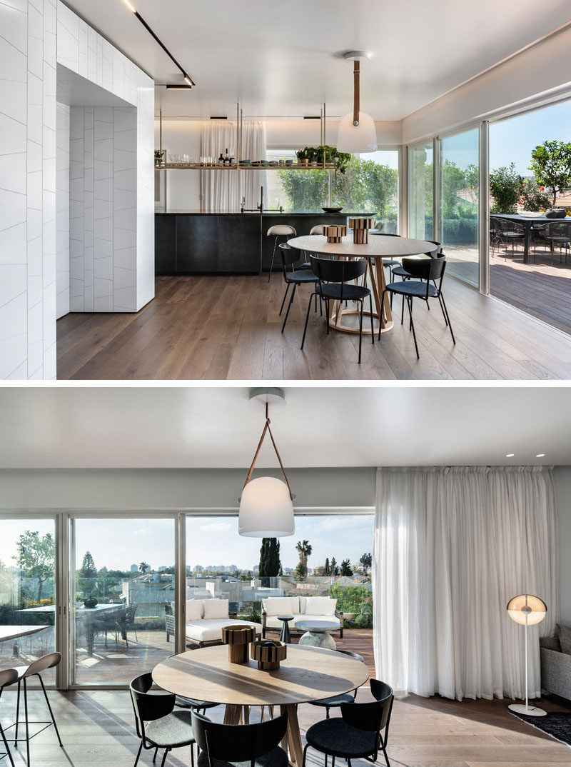 A round dining table is anchored in the room by a single pendant light in this open floor plan interior. #Apartment #DiningRoom #RoundDiningTable