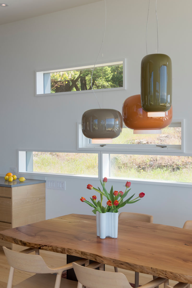 Small horizontal windows provide glimpses of the natural landscape outside. #Windows