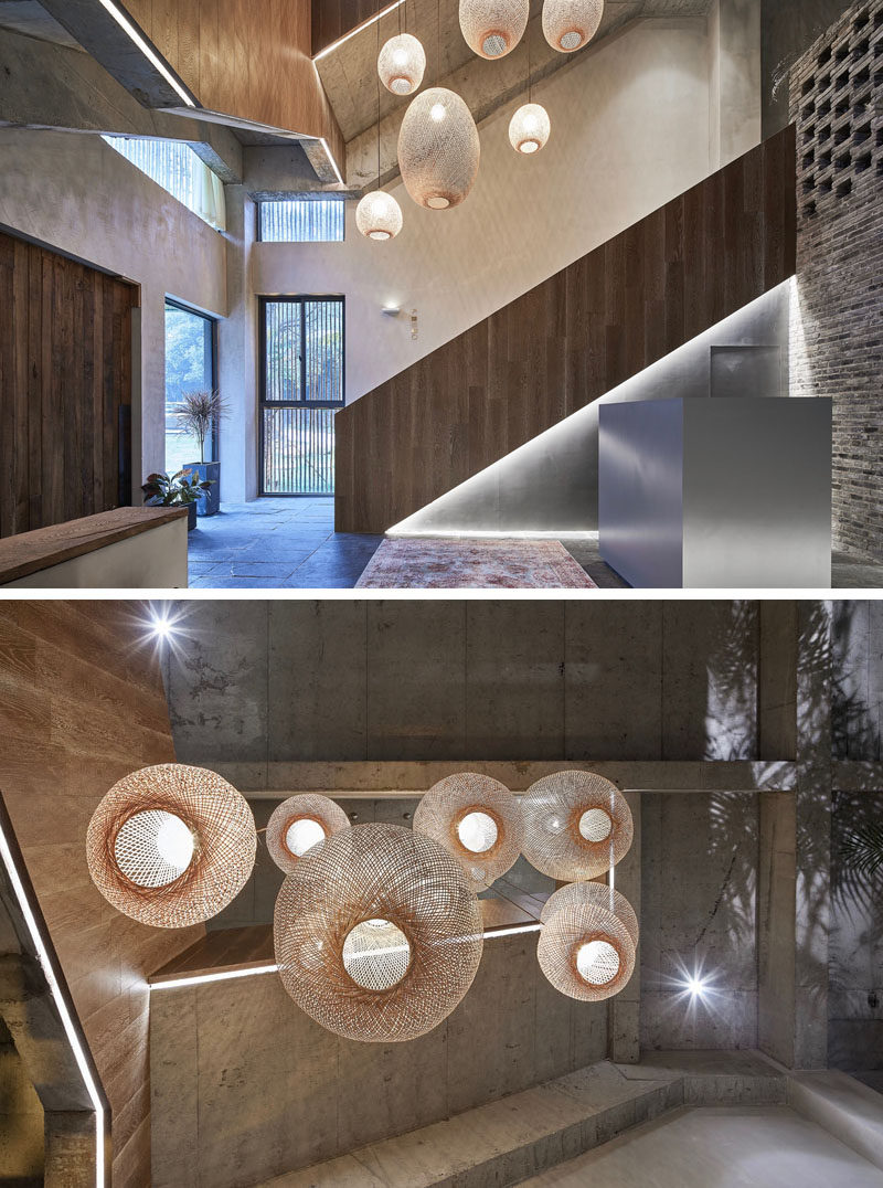 This modern hotel lobby is highlighted by a collection of woven pendant lights, while accent lighting outlines the shape of the stairs. #HotelLobby #HotelDesign #Lighting
