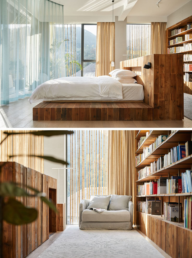 This modern hotel room has a centrally located bed that has a large wood bed frame and headboard. Behind the bed is a wood bookshelf and a small reading area. #HotelRoom #Bedroom #Bookshelf #BedFrame