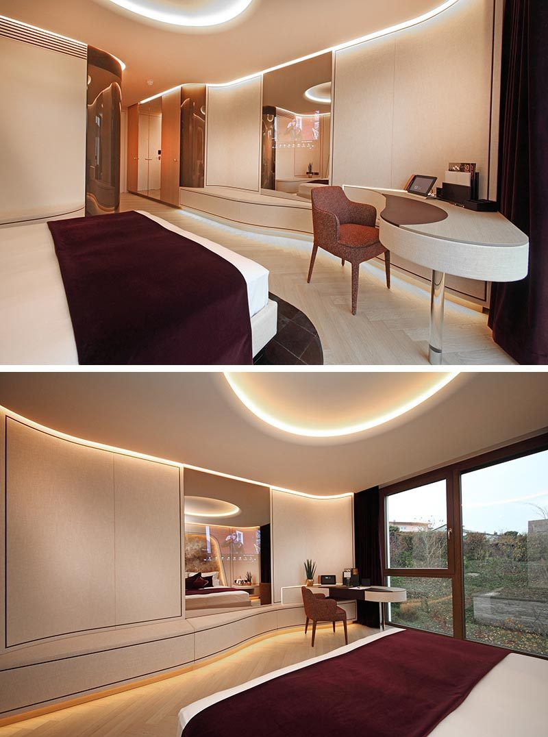 Flowing design elements, like the desk in this modern hotel room, create a soft and curvaceous line that guides the eye towards the window. #BuiltInDesk #HotelRoom #InteriorDesign