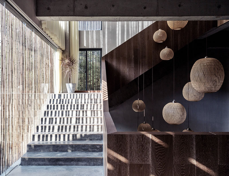 Rich wood and concrete stairs, shaded by a bamboo screen, leads to the upper floors of this modern hotel. #Stairs #ModernStairs