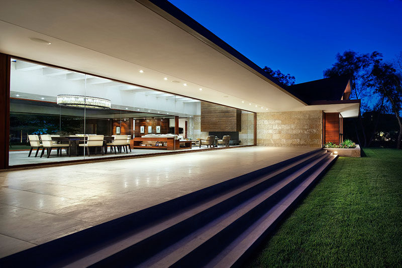 At the rear of this modern house, the large glass walls look out onto a patio that leads down to the backyard. #GlassWalls #Patio #CoveredPatio #Architecture