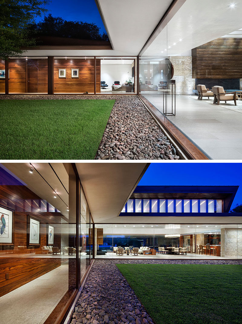 This modern house has a front lawn that's surrounded by a border of smooth pebbles, while large glass walls provide a glimpse inside. #GlassWalls #Landscaping #Lawn