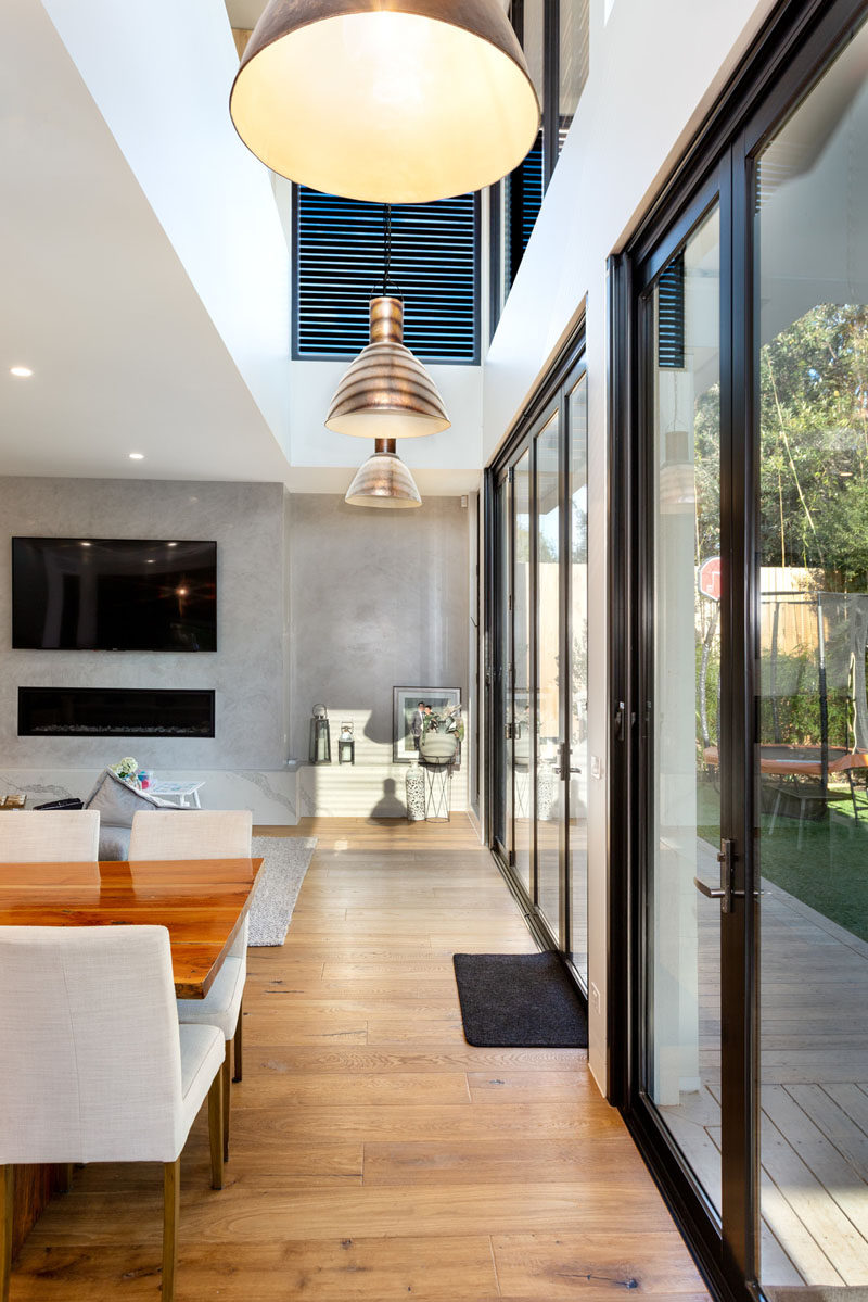 A wall of glass doors opens the interior of this modern house to the backyard, creating an indoor/outdoor environment and extending the available area for entertaining guests. #GlassDoors #InteriorDesign