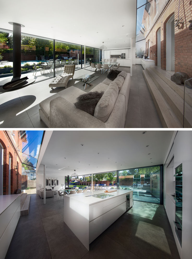 This modern extension acts as a bridge between the garden and the home, and it houses an open floor plan with a kitchen, a dining area, and a living room with a hanging fireplace. #ModernExtension #OpenPlanInterior #InteriorDesign