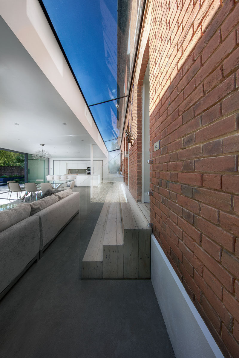 This modern extension features a 1.5m wide glass link that connects it to the original house, while three wooden steps make the transition between the two spaces easily accessible. #Skylight #Architecture #Stairs #Steps #Window #ModernExtension
