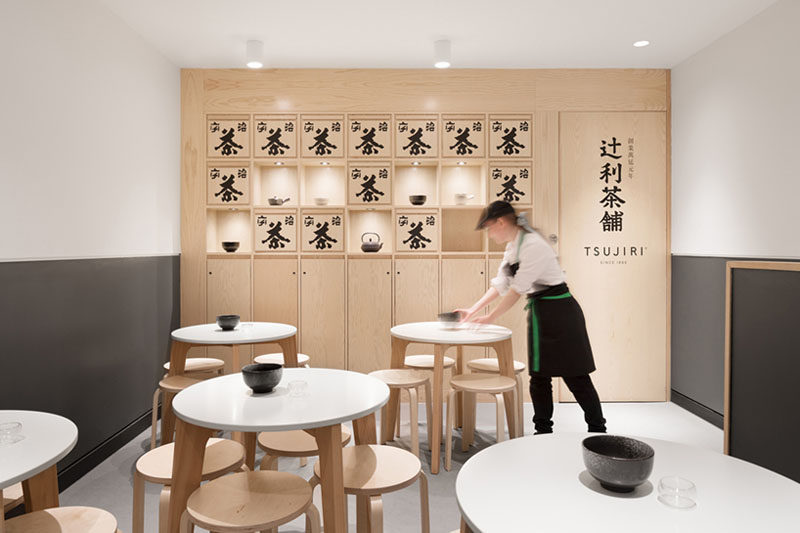This modern Japanese tea house has built-in wood display shelves, that are decorated with traditional Japanese tea boxes, while small round tables with stools provides seating for guests. #TeaHouse #ModernCafe #WoodShelving