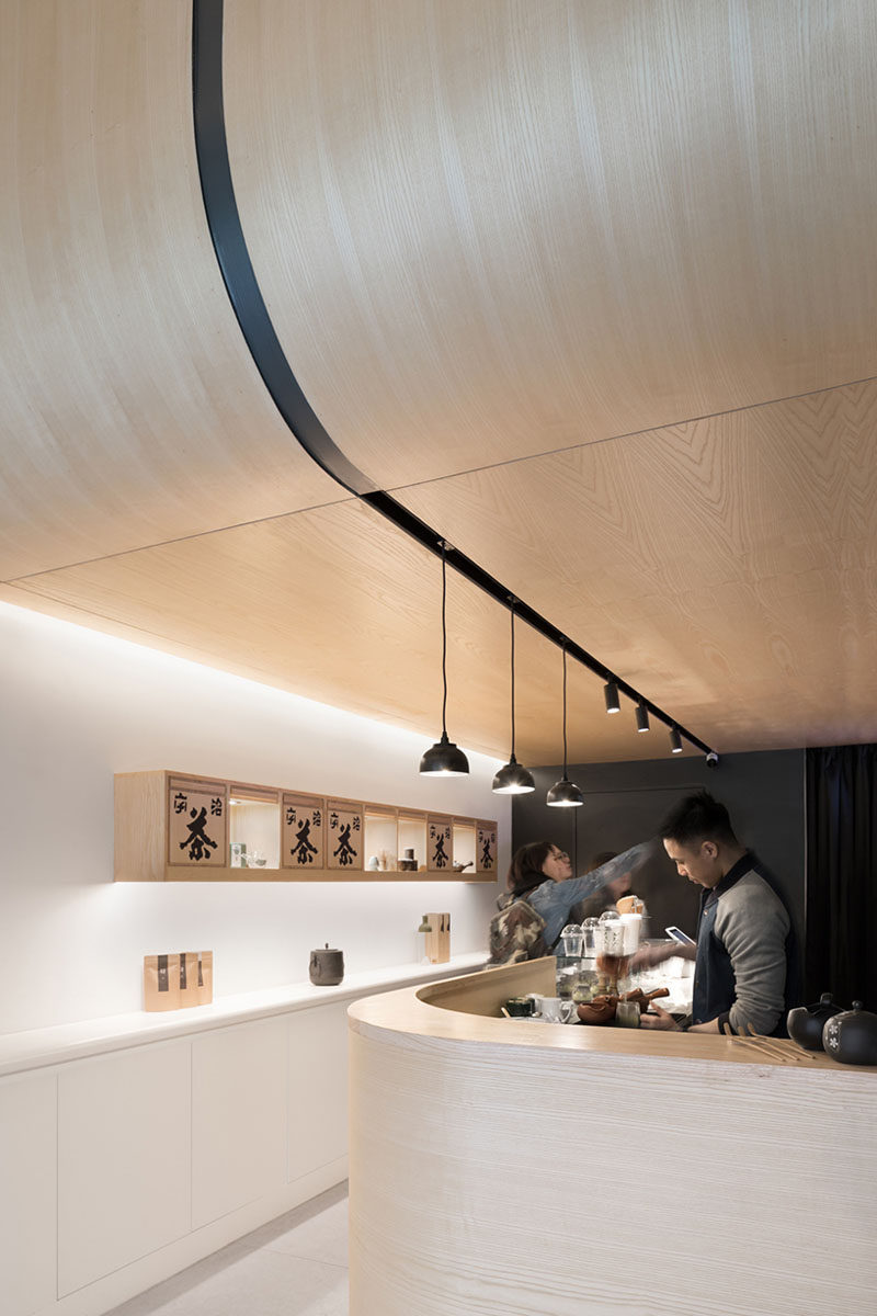 Upon entering this modern Japanese Tea House, visitors are guided straight under the curving timber ceiling where they can place their orders at the curved service counter. #CurvedWood #TeaHouse #RetailDesign