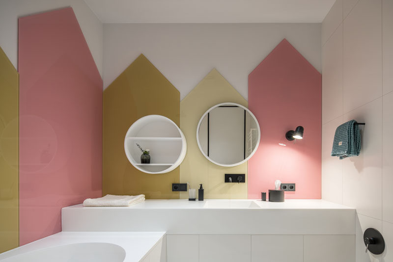 Colored glass panels in the shapes of little houses cover the walls of this kids bathroom.