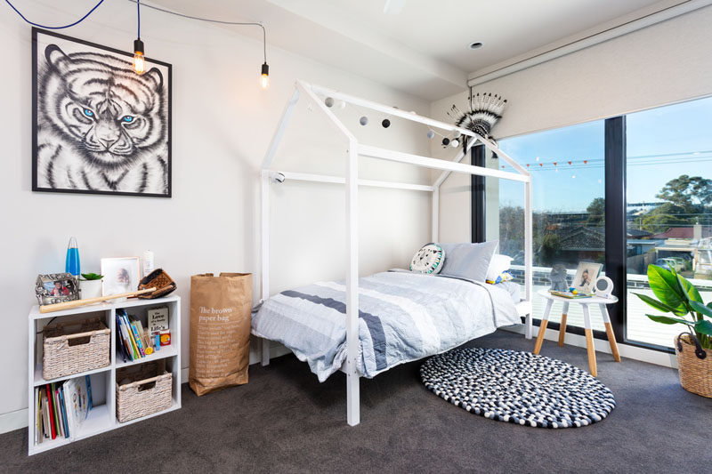 In this children's bedroom, large windows flood the room with natural light, and a dark carpet contrasts the light colored walls. #BedroomDesign #ChildrensBedroom