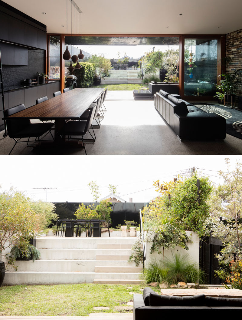 Large full height sliding glass doors open this modern interior to the backyard that has a raised outdoor dining area. #Doors #Landscaping#Backyard #SlidingGlassDoors