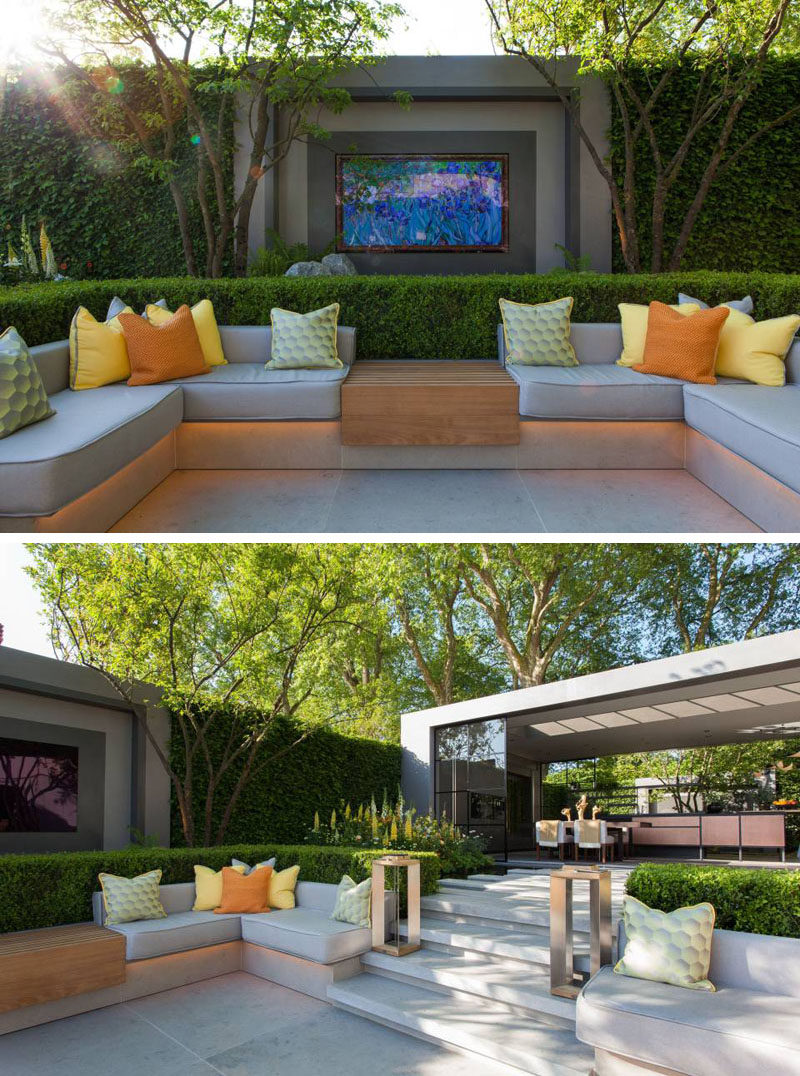 This modern garden features a sunken patio with built-in seating is surrounded by box-hedging, while stone steps leading up to a pavilion with a dining area and kitchen. #Landscaping #OutdoorSeating #SunkenLounge #GardenDesign