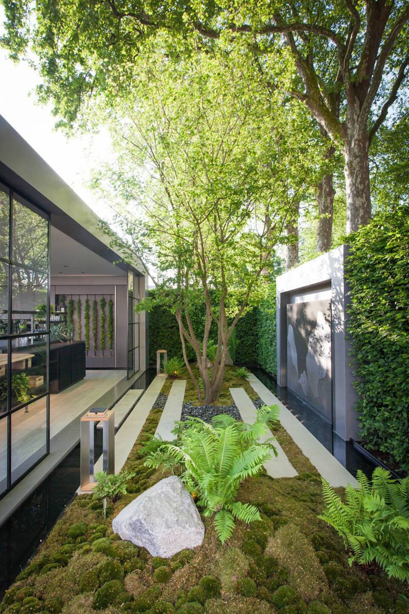 This small garden features an art piece that's surrounded by a large hedge. #ModernGarden #GardenDesign #Landscaping #LandscapeDesign
