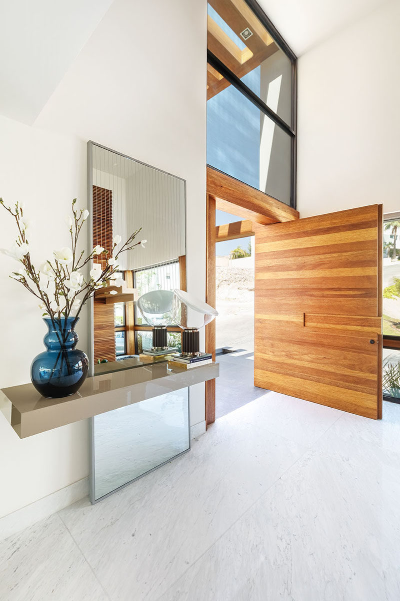 An oversized, pivoting, wood front door welcomes visitors to this modern house, and it opens up to a large double-height foyer. #WoodFrontDoor #PivotingDoor #ModernFrontDoor