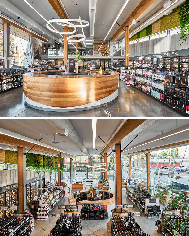 A curved wood tasting bar is centrally located within this modern liquor store. #TastingBar #RetailDesign #InteriorDesign #LiquorStore