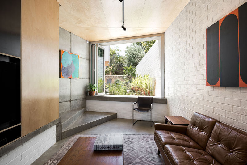 This small living room features a white brick wall, and folding windows that can be opened to provide a view of the garden. #LivingRoom #FoldingWindows