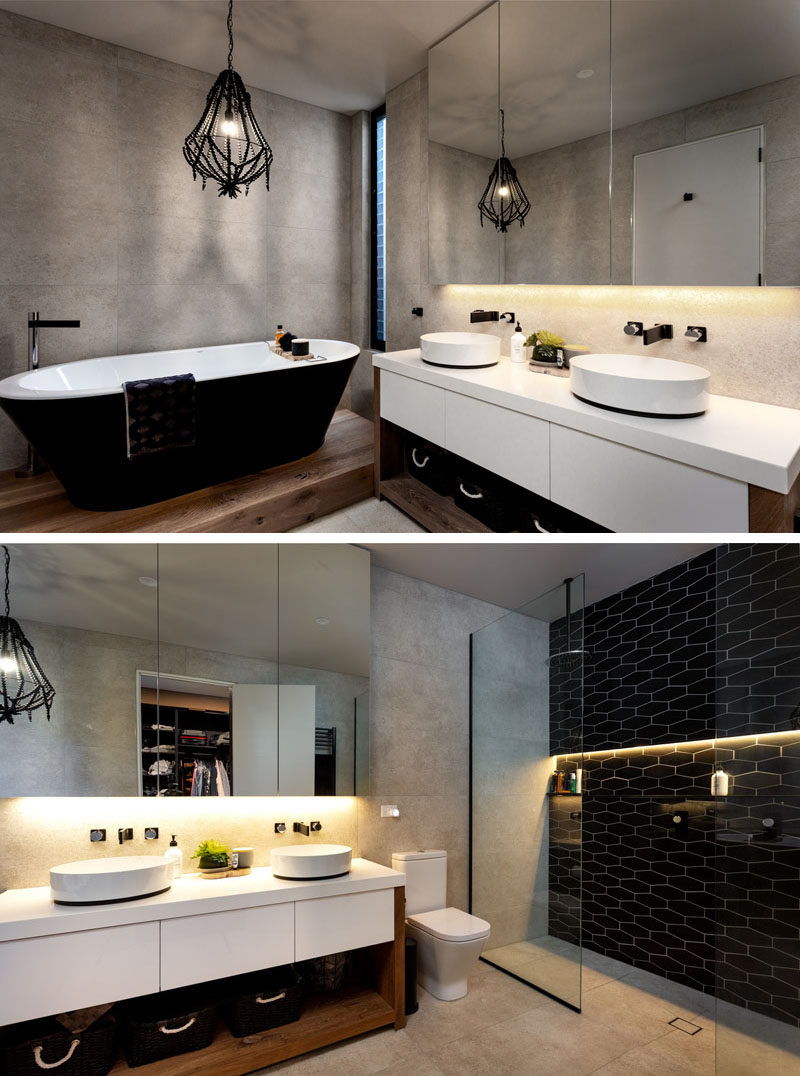 In this modern master bathroom, a black freestanding bathtub with a white interior sits below a black pendant lamp. On the other side of the vanity, a walk-in shower has a black tile accent wall with a strip of hidden lighting. #BlackBathroom #ModernBathroom #InteriorDesign