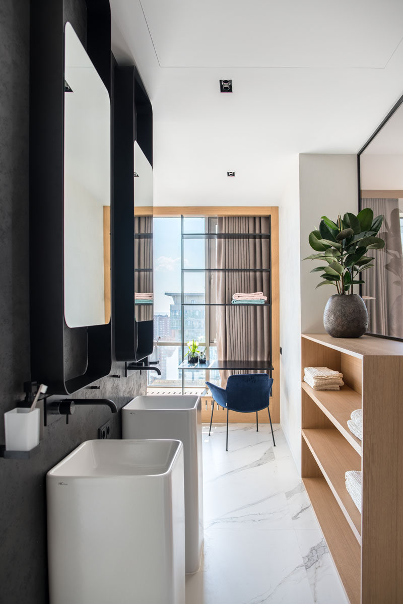 This modern ensuite bathroom features a dark accent wall, white marble tiles, wood shelving, and a desk by the window. #EnsuiteBathroom #ModernBathroom