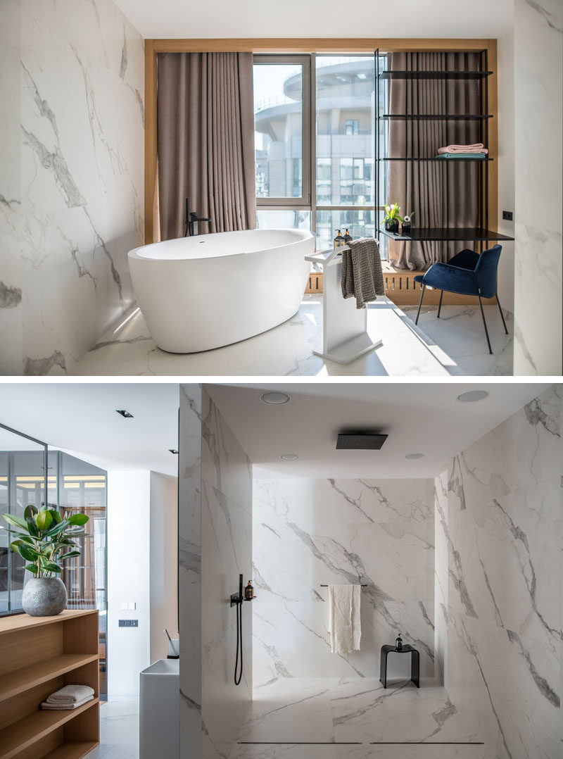 White marble tiles covering the walls and floor of this modern bathroom, while a freestanding bathtub sits in front of the window. Behind it is an open shower. #BathroomDesign #MasterBathroom #ModernBathroom
